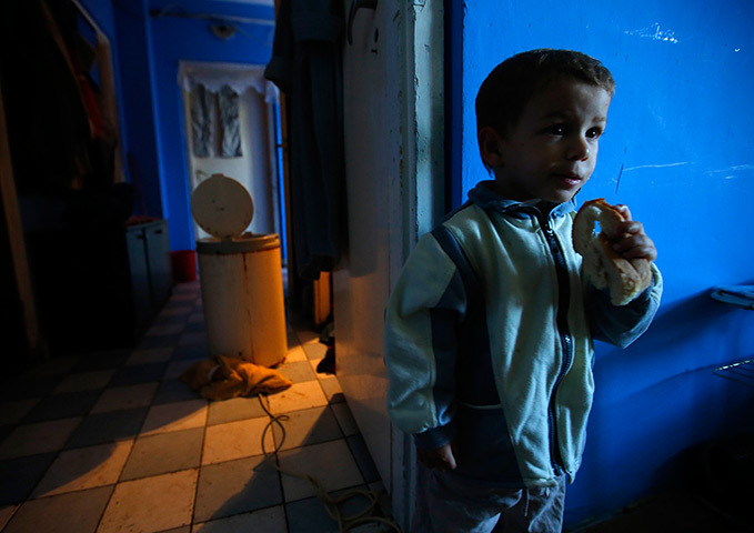 Miskolc, Hungary A Roma boy eats bread in his family's home in an apartment block (via guardian.co.uk)