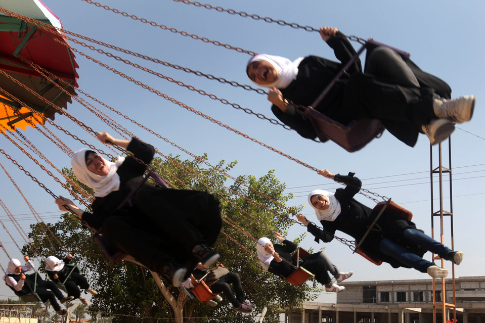 fotojournalismus:  Palestinian students rode swings at the Al-Bashir amusement park on the outskirts of Gaza City on October 18, 2012. [Credit : Majdi Fathi/Zuma Press]  We're all humans.