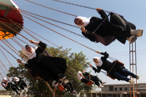 fotojournalismus:  Palestinian students rode swings at the Al-Bashir amusement park on the outskirts of Gaza City on October 18, 2012. [Credit : Majdi Fathi/Zuma Press]