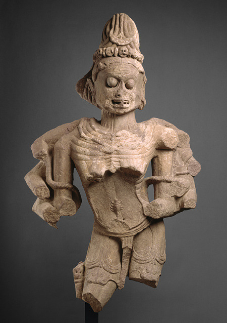astropoltergeist:  Chamunda, the Horrific Destroyer of EvilIndia, Madhya Pradesh (10th–11th century)  This is a fragment of a full-length sculpture portraying the ferocious Hindu goddess Kali in the form of Chamunda, an epithet derived from her act of decapitating the demons Chanda and Munda. Chamunda embodies bareness and decay. Her hair is piled up into a chignon decorated with a tiara of skulls and a crescent moon. She scowls, baring her teeth, and enormous eyeballs protrude menacingly from sunken sockets in her skeletal face. As a necklace, she wears a snake whose coils echo the rings of decaying flesh that sag beneath her collarbone. Just above her navel on her emaciated torso is a scorpion, a symbol of sickness and death. She presumably once held lethal objects in the hands of her twelve missing arms. Chamunda is naked except for a short diaphanous dhoti partially covering the two tiger skins complete with heads that hang from her waist to her knees. Although her extremities are missing, it is clear from comparison with related images that this Chamunda stood with legs straight, the right turned outward. The starkness and uncompromising horror of this sculpture are representative of one aspect of Indian theology.  (Source)  There's gotta be a movie featuring her somewhere out there.
