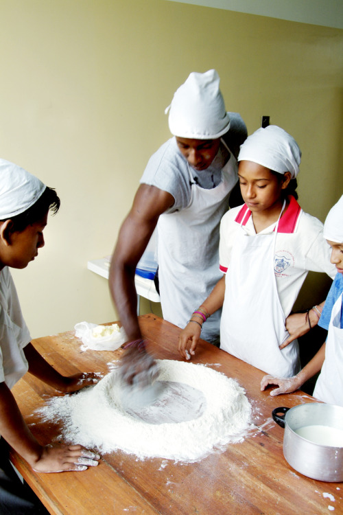 A youth development Volunteer works with children on a bakery project to help them earn money for their families as an alternative to selling candy on the street in Ecuador