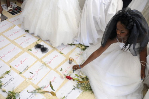 "Oct. 17, 2012. A woman places a flower onto the names of domestic violence victims during the annual ""March of Brides"" in downtown Santo Domingo, Dominican Republic."