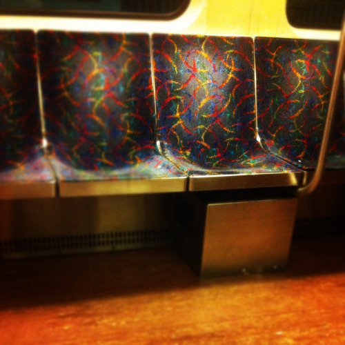 "What is your preferred seat on the train?  I think we all have one. Whether it is the seat next to the conductors booth (you can spy on them), the one nearest a door (maybe you never stay on for long), the ""Priority Seating"" chairs (hey, this is the ONE time in life where I can use a space that has a handicap sign on it and its okay!) or the one in the corner (you like to feel enclosed?); I think we all have a favorite seat to occupy as we ride public transit to and from the destinations that make up our lives. And with reason.  I happen to prefer the seat pictured above. Any seat that has a handle to the right or left of it. This is to protect me from the all to common seat encroachment. You know. That really large person who should be purchasing two airline tickets. They take up two seats on the train, too. Or the infamous bag lady, who is carrying like five different manners of tote with her, and has no problem spilling it into your lap. Or, OR! Newspaper man - you know, he has no shame in sharing section B with you, well, as a matter of fact, he is doing you a favor by sharing his morning paper!   I'm sorry, but I just can't stand the elbows and butt cheeks that all too often edge their way into what is rightfully my space. So I prefer the seat that has a bar. Because I've found that it provides an unspoken boundary. When people feel that cold metal bar against their thigh, or get their bag wrapped around it, or hit their hand turning their newspaper page, they know to reel it in just a tad.  Ahhhh. MY seat!"