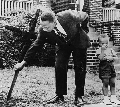 Martin Luther King Jr. removing a burning cross from his front yard, with his young son beside him. Atlanta, Georgia, 1960.