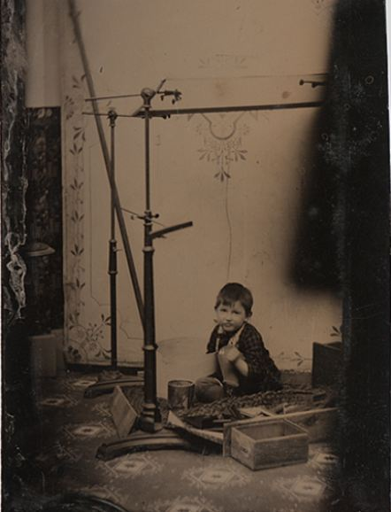 ca. 1860's-90's, [tintype portrait of a young boy, likely the photographer's son, playing in the studio among head clamps, paint, and photographic supplies] via Cowan's Auctions
