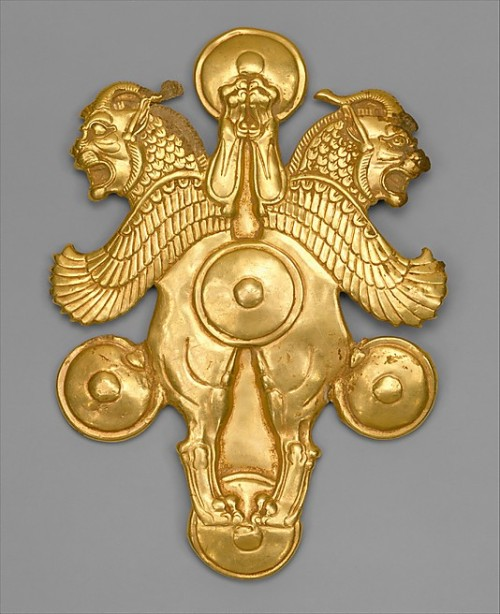Gold Plaque with horned lion-griffins Achaemenid Period c. 6th-4th Century BC Height: c.13.6 cm  Width: c. 9.8 cm This ornament depicts the winged lion-monster; the two creatures are shown rampant. In place of the lion's ears they have those of a bull. The horns curl back over spiky manes and the lion's neck is covered with a feather pattern. Sharply stylized wings extend over two of the five bosses and serve as decorative balance for the design. Heavy rings attached to the back suggest that the ornament was worn on a leather belt. the similar treatment of the lion motif on different types of objects demonstrates decorative conventions of the period. Source: Metropolitan Museum