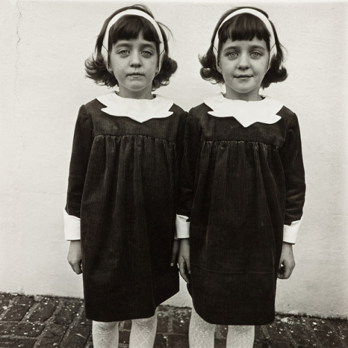 "johnsteinbeck-:  Diane Arbus, Identical Twins, Roselle, New Jersey, 1967 Identical Twins depicts two young twin sisters, Cathleen and Colleen Wade, standing side by side in matching corduroy dresses, white tights, and white headbands in their dark hair. Both stare into the camera, one slightly smiles and the other slightly frowns. The parallelism and haunting nature of the photo has been the subject of many essays. The photo has been said to sum up Arbus' vision. Biographer Patricia Bosworth said, ""She was involved in the question of identity. Who am I and who are you? The twin image expresses the crux of that vision: normality in freakishness and the freakishness in normality."" The twins were seven years old when Arbus spotted them at a Christmas party for twins and triplets. The twins' father once said about the photo, ""We thought it was the worst likeness of the twins we'd ever seen."" This photo also inspired Stanley Kubrick's image of the Grady twins in The Shining."