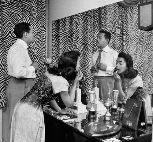 Billy Eckstine adjusting his tie while his wife June applies lipstick at a dressing table in their Manhattan apartment on April 11, 1950. The photo was taken by Martha Holmes, one of the first female staff photographers at LIFE magazine.