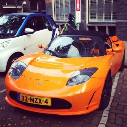 carpornpowerwomen:  Electric bright orange vehicle around the corner plugged in #carporn #tesla #motors #amsterdam #electriccar #sportscar #roadster