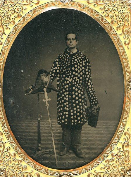 ca. 1860's, [hand tinted ambrotype portrait of gentlemen, possibly a part of the Knights Templar fraternal order, wearing an unusual disc-covered jacket, and holding a sword, mask, and hat] via Be-Hold, Fine Photographs