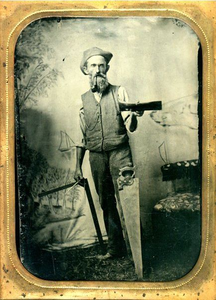 ca. 1860-90's, [tintype portrait of a bearded carpenter or shipwright, smoking a pipe, and holding a large square, compass, and the head of a large adze. A saw also leans against his leg] via Be-hold, Fine Photographs