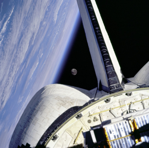 The moon is framed between the Orbiter's OMS pod and the Earth limb over the Atlantic Ocean as seen from the aft windows onboard Discovery on mission STS-95.