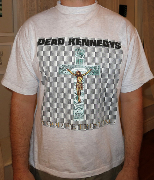 "Day: 470 Shirt: Dead Kennedys - In God We Trust, Inc. Color: Grey Brand: Blue Thunder Source:  look at the collar on this shirt, it looks like they had a hoop sewn inside it or something.  When i wear this shirt i feel like i should be hearing peoples confessions or something.  all the good old days when merch companies didn't give a shit about the fabric or the shape of a shirt.   On an entirely different subject, lets talk about this artwork and album title.  Dead Kennedys were never one to shy away form being controversial by any means.  Throwing Jesus on a Money Cross is really no exception.  I have a feeling they must have had a giant folder of good images.  Then again the 80's. Regan, Cold War so many different topics to choose from for good material.  Nowdays people aren't as clever, they try to be controversial, and may well achieve that but they don't say anything. that to me just seems like an excuse for lack of good music..  take for exaple the new Death Grips record cover for ""No Love Deep Web"" (NSFW)  Cool. you managed to be the first band to put an erect dick on your cover.  yes mothers will get mad an offended, but why? Im more offended that it is so tiny. and the handwriting is bad.  thats about it.  You know what i am saying?  If you are going to go this far at least do it for a purpose.  have two dicks fucking an 8 or something, a stand against prop 8 gay marriage.  Have it attached to  a transgender woman.  shit just maybe take a better photo of it that some crappy iphone pic.  make an attempt at art.  you are an artist after all, correct?"