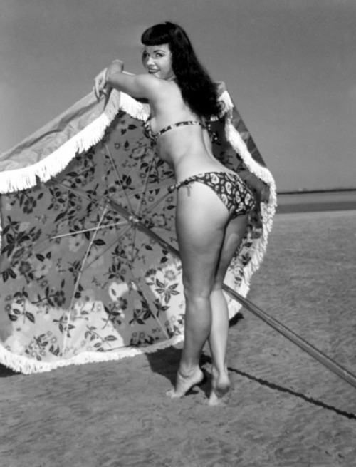 Bettie Page puts her beach umbrella up
