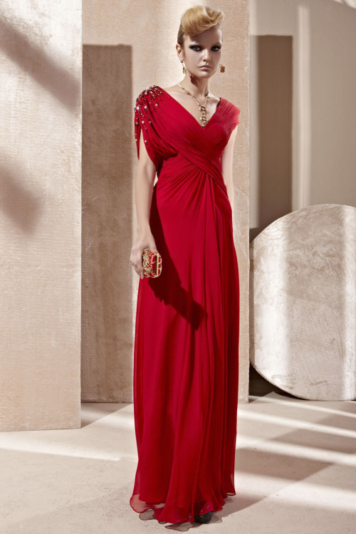 Belinda in Red V Neck Evening Dress  £330.00  Elegant red evening dress in light chiffon material featuring sleeveless A Line silhouette, high waistline, ruched bodice, V neckline, and stunning jewel embellishments on shoulder pads.