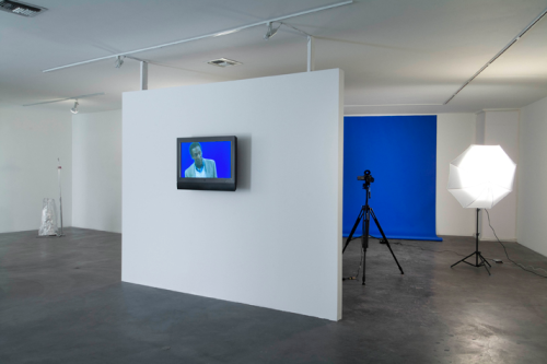 "Dave McKenzie (b. 1977) Preamble, 2009 NTSC color video with sound, chroma keyer, lights, paper, ""Ready to Die"" CD, headphones; Dimensions variable."