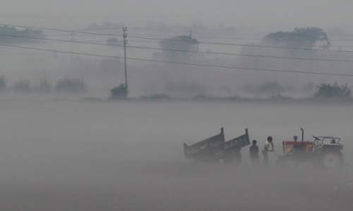 Farmers start the engine of a tractor on a foggy morning near Delhi, India. Photograph: Ahmad Masood/ Reuters