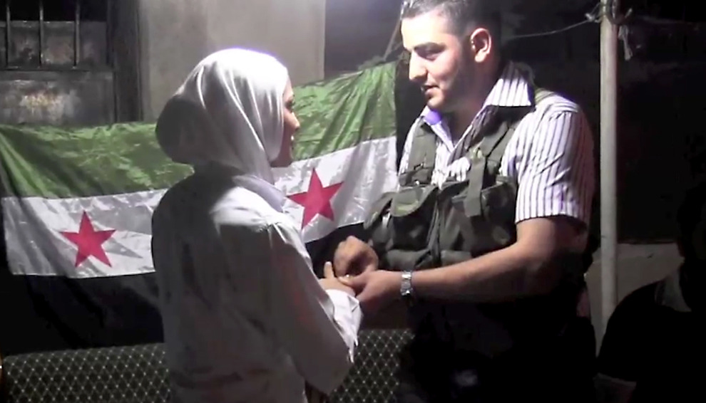 فرحة وسط أحزان #سوريا أغسطس 2012  An image grab taken from AFP TV shows Syrian rebel sniper Abu Khaled exchanging rings with his bride Hanan, the nurse who treated his leg wound, during their wedding ceremony in the Saif al-Dawla district of the northern city of Aleppo on Aug. 31. In the heart of Aleppo, besieged by Syrian troops for more than a month, a young couple who found love in the time of war exchanged vows. (James Foley/AFP/Getty Images)