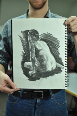 Student artist Benjamin Lange holds up a sketch completed in last Tuesday's figure drawing session. Photography by Anita To.