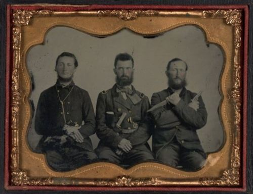 ca. 1860's, [ambrotype portrait of three soldiers; one brandishing a knife and pistol, another a very serious demeanor, and the other a complacent grin and tinted cheeks] via the San Francisco Museum of Modern Art