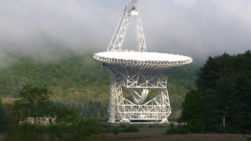 The radio telescope at the center of America's cellphone black hole MotherBoard TV has the story about the National Radio Astronomy Observatory in Green Bank, West Virginia. The observatory houses the largest steerable radio telescope in the world, with a reflector surface area of 2.4 acres. The site was originally set in Green Banks because radio telescopes are very sensitive to electromagnetic emissions (as an NRAO employee explains in the video, if a smart phone were placed on Mars, it woud appear as the brightest radio object in the sky). Green Banks in 1956 was was sufficiently remote that there were few sources of interference. Today, every wireless electronic device you own is constantly emitting EM waves. Therefore, by law, the NRAO facility is surrounded by a 13,000 square mile 'dead zone' (called the National Radio Quiet Zone) where residents and visitors are forbidden to own anything that could interfere with the facility: cellphones, WiFi, video games, radios, cars with spark plugs, even microwaves. For example, firefighters and police within the NRQZ use CB radios to communicate. Stone-age restrictions on technology aside, the NRAO has been hugely productive for the scientific community. It has tested Einstein's theories, discovered new building block molecules in space, and provides evidence as to how galaxies form. All told, the GBT (the largest telescope at the facility) observes for nearly 7000 hours every year. Unfortunately, due to the squeeze on science funding at all levels, the NRAO is at risk of being defunded. I'm sure you, my lovely followers, don't need to be reminded of risks of defunding the basic science that has made the US a leader in research and technology. Check out this neat short film about the NRAO.
