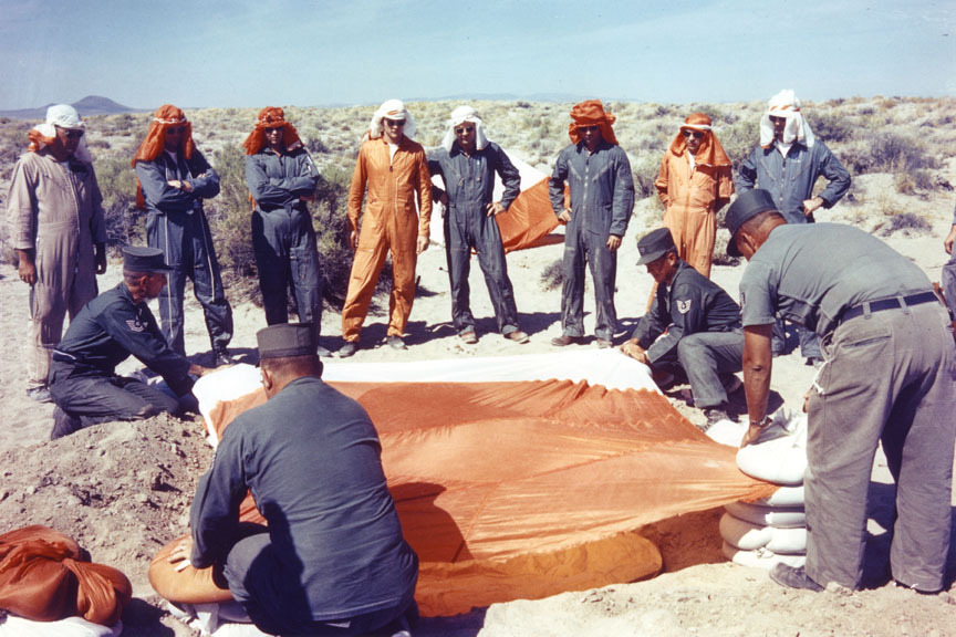lightthiscandle:  New Nine astronauts during desert survival training, 1963. Starting from the center, I believe I see Ed White, Deke Slayton (who's hiding his missing finger), John Young, Elliot See, and Jim McDivitt. I love all astronaut survival training photos. Also, John has the best parachute hat.