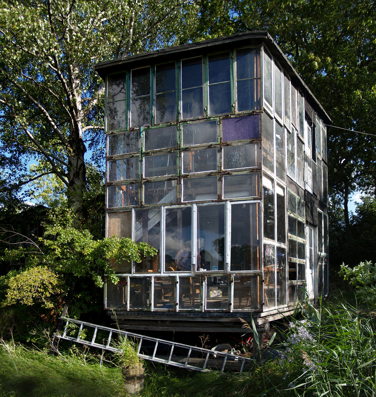 cabinporn:  A salvaged window house in Christiania, Denmark. From Tiny House Blog:  A town within a city, a rebel neighborhood within a well-ordered society. This is Christiania (Freetown), Denmark, a small community smack dab in the middle of Copenhagen, Denmark. Within this community are tiny houses, built by hand and with whatever materials are within reach. Christiania began in 1971 as an occupation of disused army barracks in the southern portion of Copenhagen near a lake. The 900 or so freethinking individuals who inhabit the area are a self governing community who refuse to pay taxes to the Danish government, run their own businesses and schools, live without cars on unpaved roads, build their own houses, restaurants and civil buildings and even have their own currency.   WE COULD DO THIS