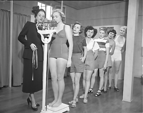 Women getting weighed at Models Academy and Finishing School with instructor, Joan Van Treel in Los Angeles, Calif., circa 1950