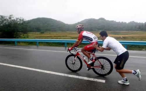 A rider gets a push back into the race. Photo: © SONG Guoqiang (via Tour Of Hainan 2012: A Rider Gets A Push Back Into The Race., Photos | Cyclingnews.com)