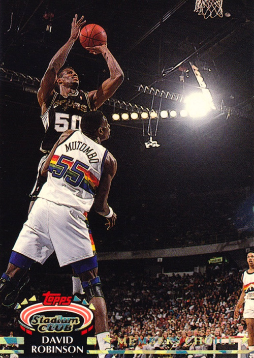 Doesn't it look like Dikembe has leg braces due to fractured bones in this card? For a defensive icon, that's pretty shitty defense. Mark Macon is shocked.