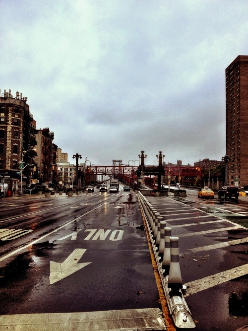 Looking down Delancey Street towards the Williamsburg Bridge during the beginning of Hurricane Sandy on Monday morning. Lower East Side, New York City.  Usually there are tons of cars and traffic at this time of morning coming off and going on to the bridge. I assume the bridges will be shut down at some point this afternoon. For now, a few cars are passing over the bridge. The winds are kicking up and the rain is a light mist.  Just went out to see if anything was open (it was: Dunkin Donuts on Delancey!). It's quite a scene out there already though. In my apartment now waiting for the worst to hit this afternoon.  In case you missed my earlier post, you can catch me on my Twitter mainly until the middle of this week unless I have to go out for some completely insane reason.  —-  View the rest of the posts about Hurricane Sandy in NYC on this blog here:  Hurricane Sandy New York City  —-  View my store, email me, ask for help, or subscribe to the mailing list.