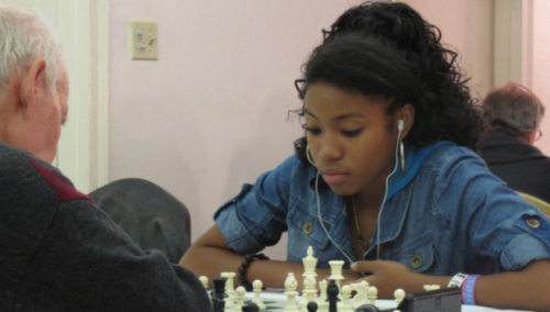 "Rochelle Ballantyne, 17, of Brooklyn is taking the chess world by storm. She is on the verge of becoming the first African-American female chess master and her journey has been documented in the film, Brooklyn Castle. Brooklyn Castle tells the stories of five members of the chess team at I.S. 318 middle school in Brooklyn.  Ballantyne, currently a senior in high school, also spoke of the budget cuts happening at I.S. 318, which would eliminate the chess program. ""Kids have achieved so much because of the chess program at I.S. 318, and now because of budget cuts, that program might not be there anymore, and that's really horrible,"" she said. ""It's so sad that you can take out money from schools because education is what allows you to succeed in life. My brother goes to I.S. 318 now, and the chess team might not be able to go to nationals. When people watch the movie, I want them to see how important the school is to all of us, and how it molded our lives. We have to pave the way so that other kids can achieve what we've achieved."" When asked about her educational goals, she has her mind-set on an Ivy League education. "" I really want to go to the University of Pennsylvania or Stanford. I applied through QuestBridge, which is a scholarship program that has a partnership with those schools."" This November, Ballantyne, has her focus on the 2012 World Youth Chess Championships to be held in Maribor, Slovenia from November 7-19."