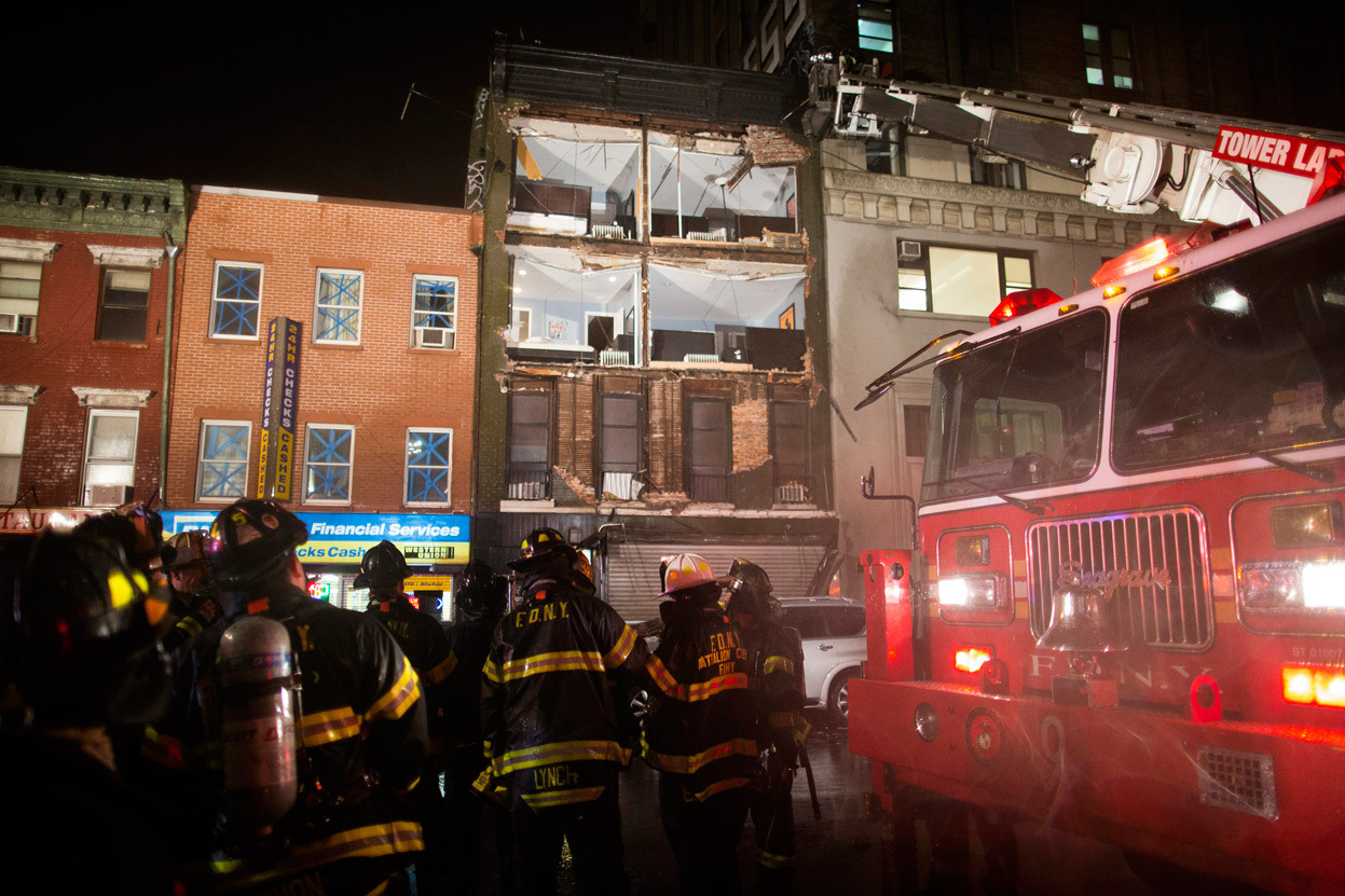Firefighters respond at the scene where the facade of a four-story building on 14th Street and 8th Avenue collapsed onto the sidewalk in New York, on October 29, 2012. (AP Photo/ John Minchillo)