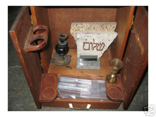 "Curious History:  The Dybbuk Box The Dybbuk Box is the commonly used name of a wine cabinet which is said to be haunted by a dybbuk, a spirit from Jewish folklore. The legend of the box originated in a story written as an eBay auction listing by Kevin Mannis. Mannis purportedly bought the Box at an estate sale in 2001. It had belonged to a Polish Holocaust survivor named Havela, who had escaped to Spain and purchased it there before emigrating to the United States. Havela's granddaughter told Mannis that the Box had been kept in her grandmother's sewing room and was never opened because a dybbuk was said to live inside it. He offered to give the box back to her, but she became upset and refused to take it.  On opening the box, Mannis found that it contained two 1920 pennies, a lock of blonde hair bound with cord, a lock of brown hair bound with cord, a small statue engraved with the Hebrew word ""Shalom"", a small, golden wine goblet, one dried rose bud, and a single candle holder with four octopus-shaped legs. Numerous owners of the box have reported that strange phenomena accompany it. His mother is supposed to have suffered a stroke on the same day he gave her the box as a birthday present. Every owner of the Box has reported that smells of cat urine or jasmine flowers and nightmares involving an old hag accompany the Box. Iosif Neitzke, a Minnesota college student and the last person to auction the box on eBay, claimed that the box caused lights to burn out in his house and his hair to fall out. Neitzke sold it to Jason Haxton, Director of the Museum of Osteopathic Medicine in Kirksville, Missouri. Haxton, who wrote The Dibbuk Box, and claimed that he subsequently developed strange health problems, including hives, coughing up blood, and ""head-to-toe welts."""