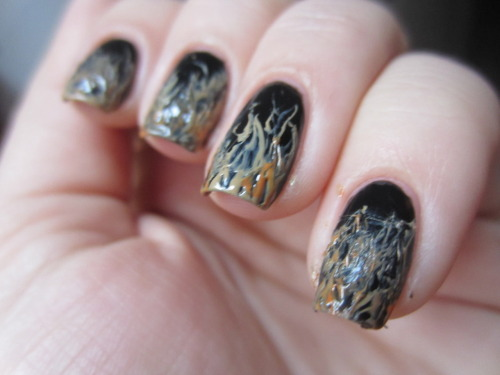 "black flame candle nails! i was watching hocus pocus when i had to do a witches nail art challenge.  so i picked the black flame candle from the movie, and coincidentally i'm watching the movie again right now! i started with a base of zoya ""raven"" which is just a black with a slight silver sheen.  then i put a thick messy french of julep ""lisa"" and used a safety pin to drag down little pin point lines.  the result looks like flames! because the black peaks through and only little lines extend upwards.  i put on accents of zoya ""jancyn"" which is an orange, to make to more flame like. what do y'all think??"