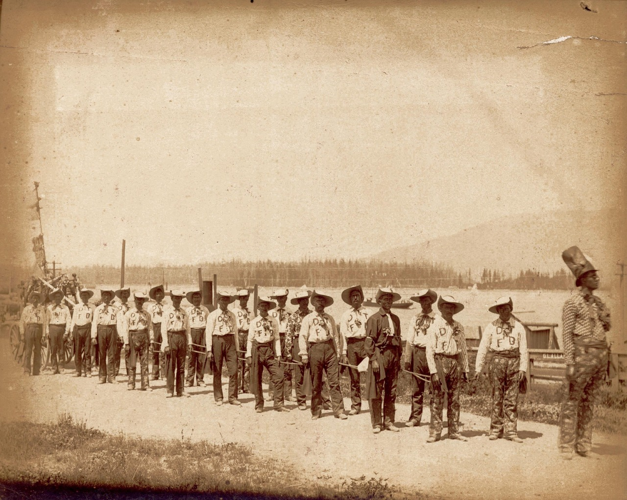 "Dark Town Fire Brigade, 1888   Photograph shows the Hastings Sawmill Volunteer Firemen Perfomance Troupe on the old Hastings Road. The first fire engine on Burrard Inlet is partially shown at the end of the troupe.   ""Dark Town and ""Dark Town Fire Brigade"" were common racist motifs in the minstrel/blackface tradition of the 19th and early 20th centuries.   Source: Photo by Bailey Bros., City of Vancouver Archives #FD P2"