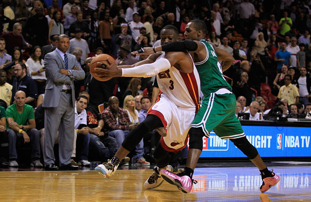 "Dwyane Wade is fouled by Rajon Rondo during the fourth quarter of last night's Heat-Celtics game. The rivalry between the two teams is strong as ever with Wade calling the foul a ""punk play."" Miami rolled to a 120-107 victory in the opening game of the NBA season. (Chris Trotman/Getty Images) THOMSEN: Miami looks ready to repeat with opening night victory"