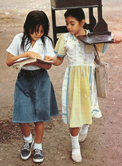 vintagenatgeographic:  Two young Nicaraguan girls tote their own desk home from a school that can't afford to provide them. National Geographic | December 1985