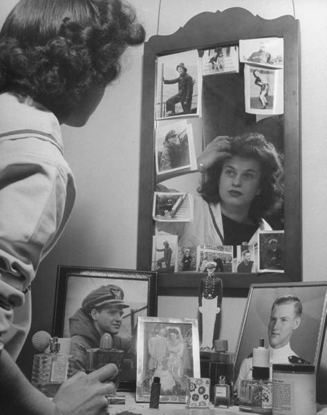 Wartime Love, 1945  Married college girl looking in mirror surrounded by pictures of her enlisted  husband.