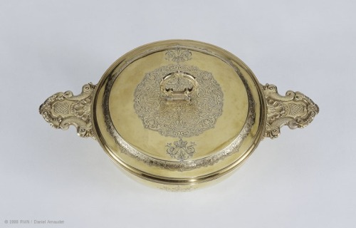 "Covered dish (porringer) Écuelle emblazoned with the arms of the Grand Dauphin, son of Louis XIV © 1988 RMN / Daniel Arnaudet @credits  Upon rising, members of the royal family would drink broth for breakfast from two-handled bowls such as these. This silver-gilt bowl is the work of the Parisian goldsmith Sébastien Leblond. It was made in 1690-2 for the Louis XIV's son, the Grand Dauphin, and is decorated accordingly: the pairs of dolphins forming the handles are, of course, the symbols of the Grand Dauphin. The chased ornamentation on the lid also incorporates dolphins either side of the intertwined letters ""L"" for Louis. The foliated scrollwork covering the center of the lid is characteristic of designs used by goldsmiths in the reign of Louis XIV."