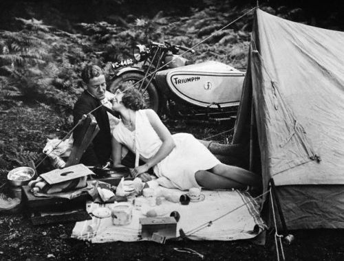 A couple on a Triumph motorbike camping tour break for a picnic, ca. 1935.