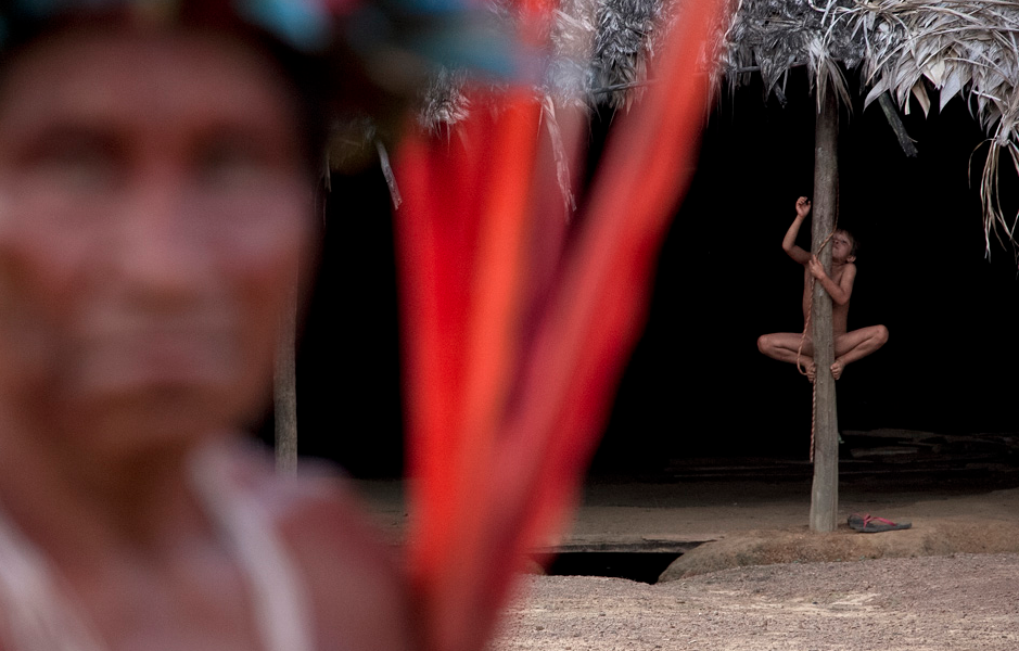A Yanomami Indian boy plays as adults gather for a meeting of tribal members from two different villages, in Novo Demini on the border between the states of Amazonas and Roraima, October 14, 2012. Some 150 of the Yanomami met as leaders and government representatives discussed ways to improve their health and education on the 20th anniversary of the creation of their Yanomami Indian Reserve. REUTERS/Odair Leal