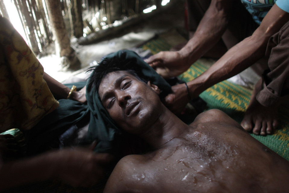 Mohammad Nur, 28, lay in a faint at a house in Taknaf, Bangladesh, where he was hiding from border officials with his wife and son Tuesday. Mr. Nur, a Rohingya Muslim from Myanmar, said he walked a day and night with his family to Bangladesh, fleeing violence in Myanmar. Andrew Biraj/Reuters