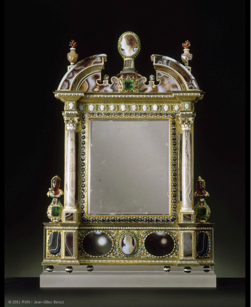 "Rock-crystal mirror C. 1630 Paris   Frame: sard, agate, sard cameos, rubies, diamonds, emeralds, garnets, enamelled gold H. 40 cm; W. 28.30 cm; D. 5 cm   Purchased by Louis XIV in 1684 to the marchand Le Brun MR 252  @credits   The mirror was purchased by Louis XIV in 1684 from the dealer Le Brun at the same time as the sconce MR 251. It comprises several pieces of sard and cameos. The stones are set off by a metalwork mount in the style of Pierre Delabarre, a 17th-century goldsmith. This work reflects the interest of 17th-century collectors in hard stone and the richness of Louis XIV's collection of precious and semiprecious stones. Cameos and sard to frame a mirror The rectangular rock-crystal mirror is set in a frame decorated with pieces of sard, probably reused stones. The shape of the frame is evocative of a window recess or frame. It comprises a discontinuous arched pediment supported by two small columns, and a base. The two molded elements forming the pediment may have come from ancient vases; the gray agate columns were possibly produced as part of the decoration of a cabinet; and the two small vases at the top corners were probably carved from reused agate eggs. The cameos date from the Renaissance. The agate cameos on the frieze depict the twelve Caesars facing each other two by two; the cameo at the center of the base shows Diana's head in profile; and the cameo in the center of the pediment represents a woman's head, also in profile. At the foot of the columns set against a metal strip are two busts in garnet that are similar to a garnet and gold bust of a warrior kept in the Bibliothèque Nationale de France. A mount in enameled gold and precious stones The mount has the same characteristics as the sconce MR 251. It features small openwork leaves and enameled gold seeds. The enamel is both opaque (white, light green, light blue, mauve) and translucent (dark blue, green, orange, red, black). The enamel decoration is located at the base and runs around the mirror itself and the precious stones. The pea-pod motif -common in goldwork in the first half of the 17th century - is also present, especially on either side of the Diana cameo. The capitals and the bases of the columns also feature painted white enamel decorated with polychrome palmettes and seeds. The decoration is similar to that surrounding the base of the ewer MR 445. A mount in the style of Delabarre Collectors of hard stones liked to enhance them with metalwork mounts. Two styles of mount were favored in 17th-century France: the ""Delabarre"" style, after the goldsmith Pierre Delabarre, and a more classical style. The mirror in the Louvre is representative of the ""Delabarre"" style. At the time, there existed collections of model bouquets made up of small cutout leaves with trefoil, pointed, or rounded shapes, often hollowed out. Inside the bouquets were strings of seeds and pea pods. One of the ornamentalists who created such bouquets was Pierre Delabarre, who was appointed master goldsmith in Paris in 1625 and granted lodgings at the Louvre. The bouquets were reworked in precious metals by goldsmiths. The pieces of sard and the cameos are assembled on gilded brass plaques and joined up with small enameled gold leaves in the style of Delabarre - some of them hollowed out - in opaque or translucent enamel. This mount is also dotted with white seeds. This decoration is very similar to that of the sconce purchased by Louis XIV at the same time."