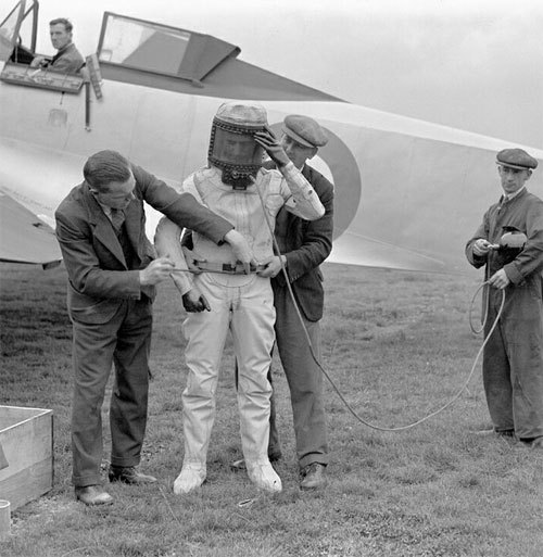 """Squadron Leader F.R.D. Swain is helped into his high altitude pressure helmet in front of his charge, the Bristol Type 138A, K4879, Farnborough, 10 September 1936"" (via FlightGlobal)"
