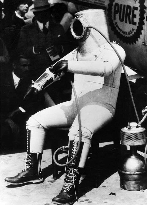"""Wiley Post shows off his inflated full-pressure suit in front of the Winnie Mae. Note the wingnut on Post's shoulder, just behind the helmet.The oxygen generator is on the ground next to Post, connected to the left side of the visor.The position of Post's arms shows the relative stiffness of the inflated suit, something that would hamper pressure suit development for another 50 years.""   Photo from an incredible free download of ""Dressing for Altitude U.S. Aviation Pressure Suits–Wiley Post to Space Shuttle"", by Dennis R. Jenkins"