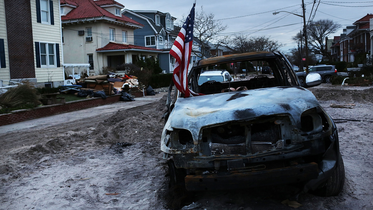 A burned truck holds an American flag in Rockaway, Queens. Photo Credit: Getty Images