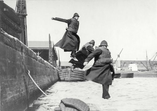 Port of London Authority policemen testing life-jackets by jumping into the water at the West India Docks, in around 1930.