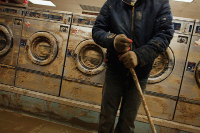 fotojournalismus:  Eddie Liu cleans up a launderette after flooding caused by superstorm Sandy in the Coney Island neighbourhood of New York, November 2, 2012. [Credit : Lucas Jackson/Reuters]