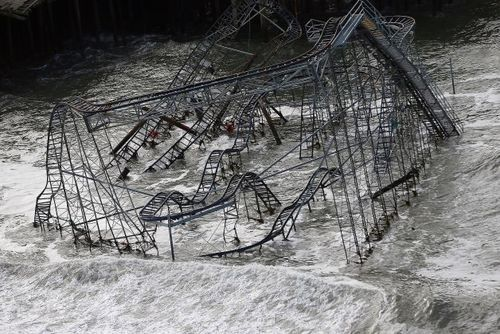 Surf rolls past a destroyed roller coaster wrecked by Superstorm Sandy on October 31, 2012 in Seaside Heights, New Jersey — Getty Images.